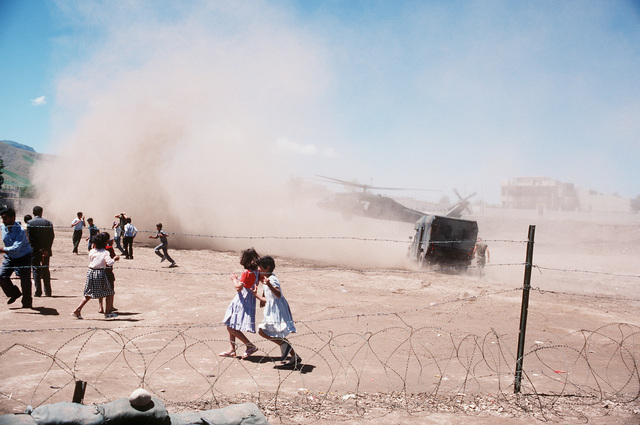 Kurdish children hurry away from the dust stirred up by a UH-60 Black Hawk helicopter as it touches down at a tent city. Allied forces are setting up the camp site, the first to be constructed as part of Operation Provide Comfort, an effort to aid Kurdish refugees who fled from the forces of Saddam Hussein in northern Iraq
