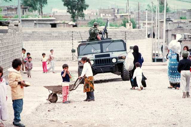 Kurdish children play near an Army M1038 High-Mobility Multipurpose Wheeled Vehicle (HMMWV) as it patrols the streets of the city. U.S. and coalition troops are in Zakhu as part of Operation Provide Comfort, a multinational effort to aid Kurdish refugees in northern Iraq and southern Turkey