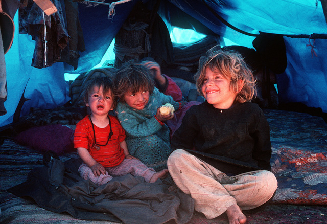 Kurdish children sit in their family's tent at a refugee camp near the Turkey-Iraq border. Thousands of Kurds fled into Turkey after fighting broke out between Kurdish groups and Iraqi government forces following Operation Desert Storm. Troops from the U.S. and other nations have come to the camp to distribute aid and prepare the refugees for a move to organized camps within Iraq as part of Operation Provide Comfort