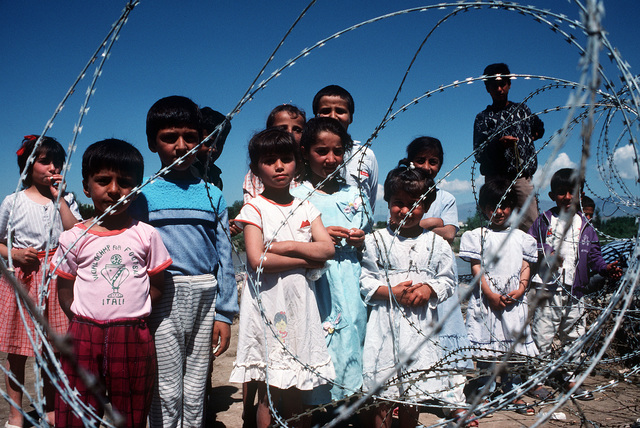 Kurdish children standing behind concertina wire watch as Marines set up a tent city. Allied forces are setting up the camp site, the first to be constructed, as part of Operation Provide Comfort, an effort to aid Kurdish refugees who fled from the forces of Saddam Hussein in northern Iraq