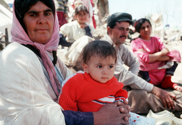 Kurdish families pass the time at a refugee camp near the Turkey-Iraq border. Thousands of Kurds fled into Turkey after fighting broke out between Kurdish groups and Iraqi government forces following Operation Desert Storm. Troops from the U.S. and other nations have come to the camp to distribute aid and prepare the refugees for a move to organized camps within Iraq as part of Operation Provide Comfort