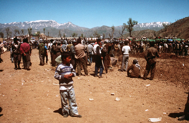 Kurdish men at a refugee camp near the Turkey-Iraq border gather outside a barbed-wire enclosure to pick up food for their families. Thousands of Kurds fled into Turkey after fighting broke out between Kurdish groups and Iraqi government forces following Operation Desert Storm. Troops from the U.S. and other nations have come to the camp to distribute aid and prepare the refugees for a move to organized camps within Iraq as part of Operation Provide Comfort