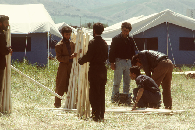 Kurdish men gather support poles to erect additional tents at a refugee camp near Zakhu, Iraq. U.S. and allied troops established the camp as part of Operation Provide Comfort, a multinational effort to aid the thousands of Kurds who fled their homes after fighting broke out between Kurdish groups and Iraqi government forces following Operation Desert Storm