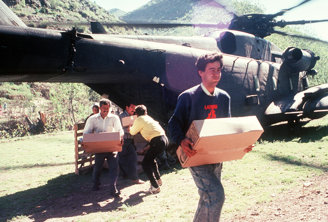 Kurdish men help unload cases of rations from the back of a Marine Corps CH-53E Super Stallion helicopter during Operation Provide Comfort, a multinational effort to aid Kurdish refugees in southern Turkey and northern Iraq