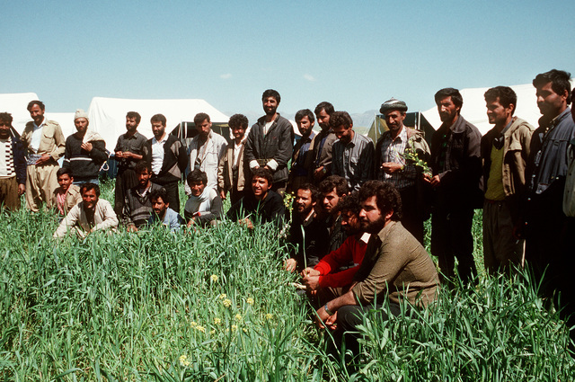 Kurdish men listen to a briefing after arriving at a refugee camp near Zakhu, Iraq. U.S. and allied troops established the camp as part of Operation Provide Comfort, a multinational effort to aid the thousands of Kurds who fled their homes after fighting broke out between Kurdish groups and Iraqi government forces following Operation Desert Storm