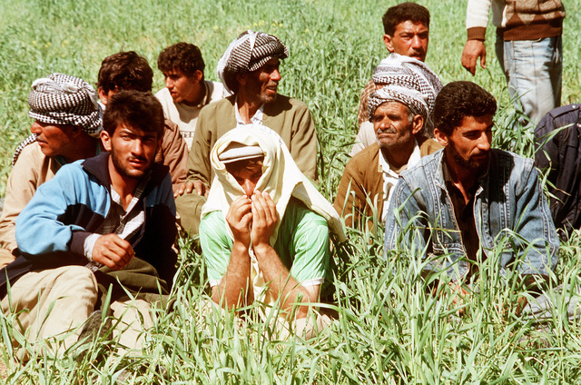 Kurdish men sit in the grass after arriving at a refugee camp near Zakhu, Iraq. U.S. and allied troops established the camp as part of Operation Provide Comfort, a multinational effort to aid the thousands of Kurds who fled their homes after fighting broke out between Kurdish groups and Iraqi government forces following Operation Desert Storm