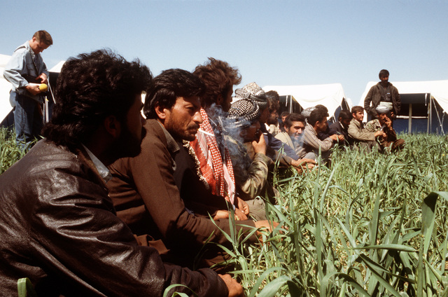Kurdish men sit in the grass next to some tents at a refugee camp near Zakhu, Iraq. U.S. and allied troops established the camp as part of Operation Provide Comfort, a multinational effort to aid the thousands of Kurds who fled their homes after fighting broke out between Kurdish groups and Iraqi government forces following Operation Desert Storm