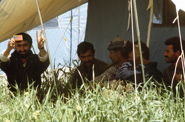 Kurdish men sit in the shade beneath a tent fly at a refugee camp near Zakhu, Iraq. U.S. and allied troops established the camp as part of Operation Provide Comfort, a multinational effort to aid the thousands of Kurds who fled their homes after fighting broke out between Kurdish groups and Iraqi government forces following Operation Desert Storm