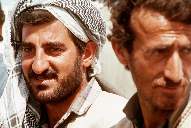 Kurdish men wait to begin a tour of a refugee camp near Zakhu, Iraq. U.S. and allied troops established the camp as part of Operation Provide Comfort, a multinational effort to aid the thousands of Kurds who fled their homes after fighting broke out between Kurdish groups and Iraqi government forces following Operation Desert Storm