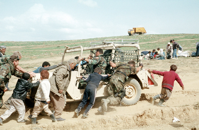 Kurdish refugee children and and old man help U.S. military personnel dislodge a light vehicle from a rut. The U.S. forces are in the region as part of Operation Provide Comfort, an Allied effort to aid the refugees who fled the forces of Saddam Hussein in northern Iraq