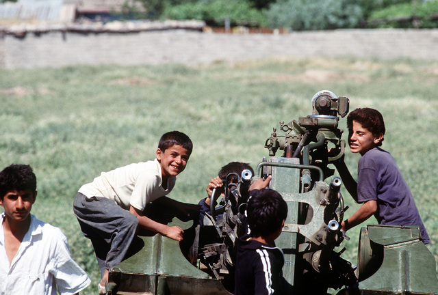 Kurdish refugee children play on a Soviet-built ZPU-4 anti-aircraft gun which was abandoned by Iraqi forces during Operation Desert Storm. The children live in a nearby camp established as part of Operation Provide Comfort, an Allied effort to aid the refugees who fled the forces of Saddam Hussein in northern Iraq