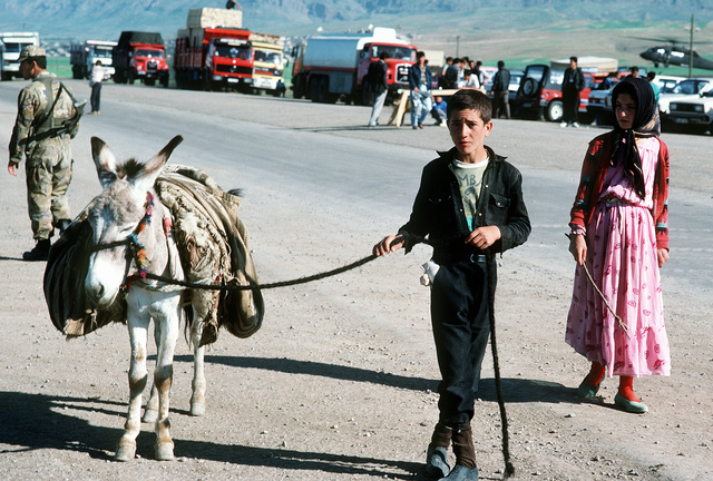 Kurdish refugee children walk along a road near the first established tent city along the Turkey-Iraq border, under construction as part of Operation Provide Comfort. Allied forces are constructing the tent city in an effort to aid Kurds who fled from the forces of Saddam Hussein in northern Iraq