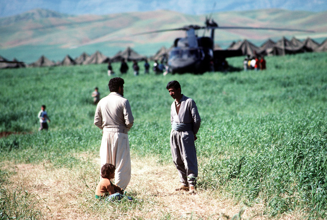 Kurdish refugees converse in a field beside a tent city on the outskirts of Zakhu as an UH-60 Black Hawk helicopter delivers supplies in the background. The encampment was established as part of Operation Provide Comfort, an Allied effort to aid those fleeing the forces of Saddam Hussein in northern Iraq