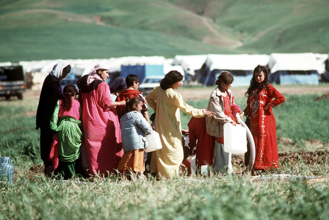 Kurdish refugees fill containers with purified water on the outskirts of their tent city near Zakhu. Such necessities are being proved as part of Operation Provide Comfort, an Allied effort to aid those fleeing the forces of Saddam Hussein in northern Iraq