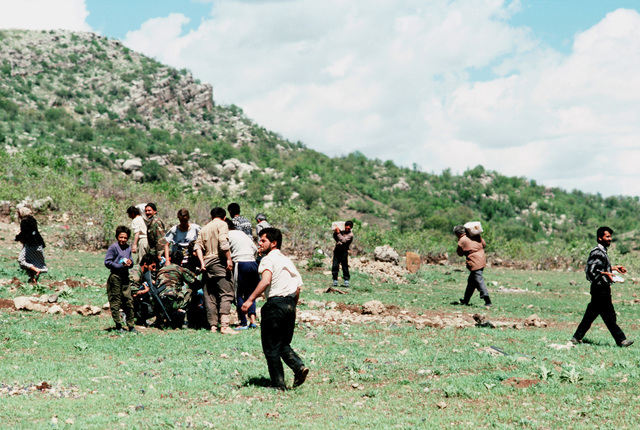 Kurdish refugees gather a U.S. soldier as they move supplies from a landing zone to a camp. The material is being provided as part of Operation Provide Comfort, an Allied effort to aid the refugees who fled from the forces of Saddam Hussein in northern Iraq