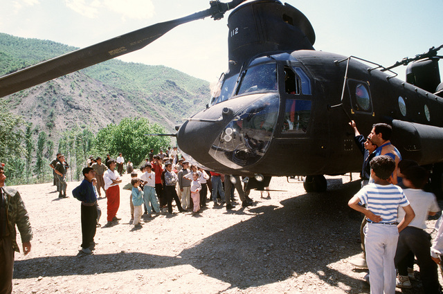 Kurdish refugees prepare to board a U.S. Army CH-47 Chinook helicopter for transportation from their mountain camp to a newly established tent city near Zakhu. The tent city was established as part of Operation Provide Comfort, an Allied effort to aid Kurdish refugees who fled the forces of Saddam Hussein in northern Iraq