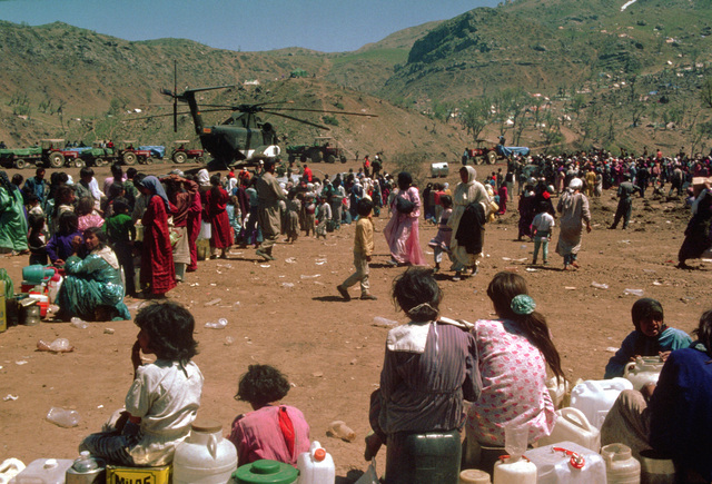 Kurds at a refugee camp near the Turkey-Iraq border wait in line near a German army CH-53G helicopter to receive an allotment of water. Thousands of Kurds fled into Turkey after fighting broke out between Kurdish groups and Iraqi government forces following Operation Desert Storm. Troops from the U.S. and other nations have come to the camp to distribute aid and prepare the refugees for a move to organized camps within Iraq as part of Operation Provide Comfort