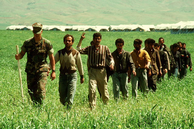 Led by Marine STAFF SGT. T.J. Lewnes, a group of Kurdish men crosses a field while touring a refugee camp near Zakhu, Iraq. U.S. and allied troops established the camp as part of Operation Provide Comfort, a multinational effort to aid the thousands of Kurds who fled their homes after fighting broke out between Kurdish groups and Iraqi government forces following Operation Desert Storm