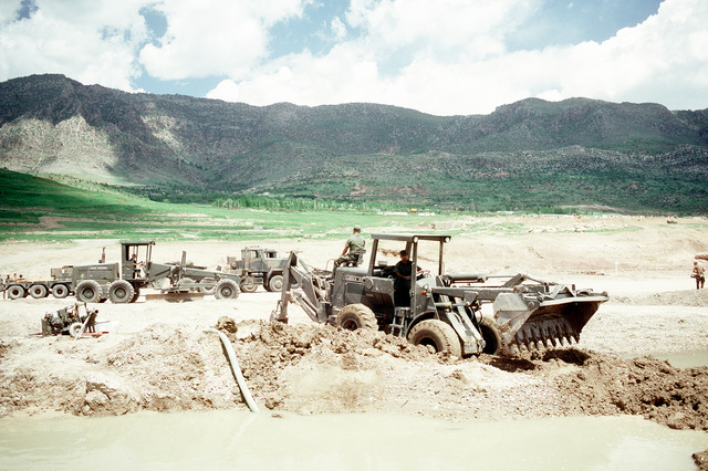 Members of an air detachment from Naval Mobile Construction Battalion 133 (NMCB-133) use a loader equipped with a backhoe to clear a drainage area as they repair an Iraqi airfield. The Seabees are repairing the airfield, which had been under construction prior to the start of the Persian Gulf war, to allow relief supplies to be flown in for nearby Kurdish refugees as part of Operation Provide Comfort