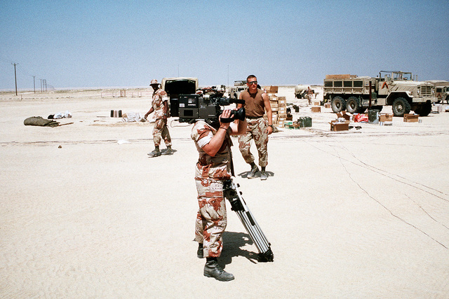 """Photographer's Mate 2nd Class Keith Tayman, videographer for the Navy's television program """"Navy News This Week,"""" films a convoy of Marine vehicles of Headquarters Battalion, 2nd Marine Division. The Marines are moving out to Jubail, Saudi Arabia after being stationed west of Kuwait City during Operation Desert Storm"""