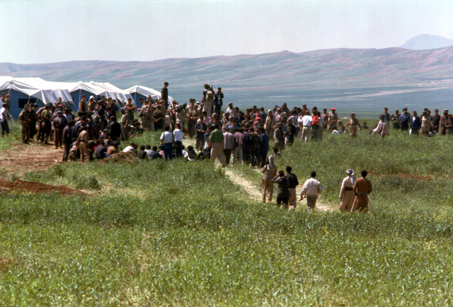 Soldiers, journalist and Kurds gather on a hillside for a briefing at a refugee camp near Zakhu, Iraq. U.S. and allied troops established the camp as part of Operation Provide Comfort, a multination effort to aid the thousands of Kurds who fled their homes after fighting broke out between Kurdish groups and Iraqi government forces following Operation Desert Storm