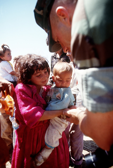 SSGT Lee Tibbits shares a snack with Kurdish refugee children at their tent city in Zakhu. The camp was established as part of Operation Provide Comfort, an Allied effort to aid Kurdish refugees who fled the forces of Saddam Hussein in northern Iraq