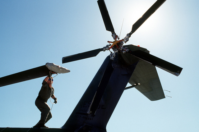 SSGT Wayne C. Giffen, flight engineer, 71st Air Rescue Squadron (71st ARS), prepares to anchor tail rotor blades on an HH-3E Jolly Green Giant helicopter as the HH-3E is secured for the night. The helicopter is stopping over at Malmstorm en route to Aircraft Maintenance and Regeneration Center at Davis-Monthan Air Force Base, Arizona, where the HH-3E is being relocated in preparation for the squadron's deactivation on June 1, 1991. The 210th Rescue Squadron, Air National Guard, will take over Alaskan rescue missions