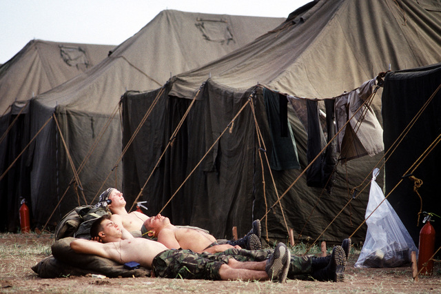 Three off-duty servicemen relax in the sun between two rows of tents at the humanitarian services support base established for Operation Provide Comfort, a multinational effort to aid Kurdish refugees in northern Iraq and southern Turkey