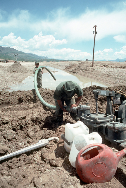 Two members of an air detachment from Naval Mobile Construction Battalion 133 (NMCB-133) set up a gasoline-powered pump to drain the water from a bomb crater in the runway at an Iraqi airfield. The Seabees are repairing the airfield, which had been under construction prior to the start of the Persian Gulf war, to allow relief supplies to be flown in for nearby Kurdish refugees as part of Operation Provide Comfort