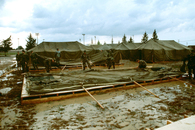 U.S. Air Force and Army personnel wade through mud to raise tents on platforms that will house personnel deployed in support of Operation Provide Comfort. Fifty 20-man tents are being erected on the air base site.