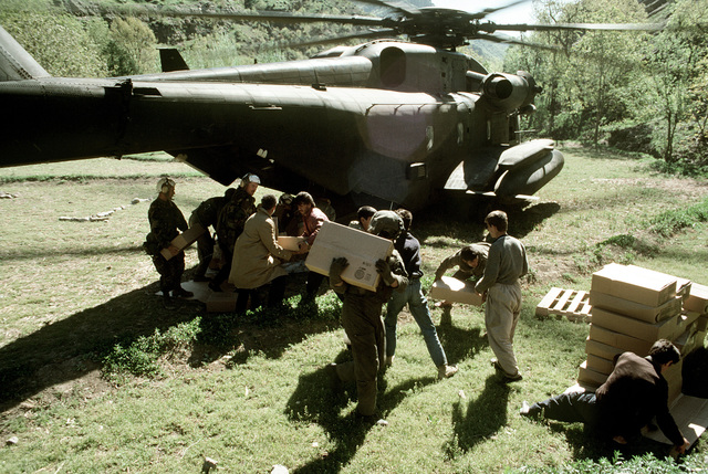 U.S. military personnel and Kurdish refugees unload supplies from a CH-53E Super Stallion helicopter. Military personnel are in the area as part of Operation Provide Comfort, an Allied effort to aid the refugees who fled from the forces of Saddam Hussein in northern Iraq