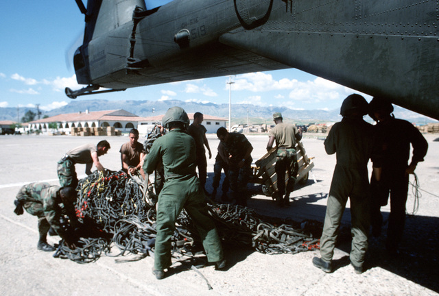 U.S. military personnel prepare to load supplies onto a CH-53E Super Stallion helicopter. The material will be delivered to Kurdish refugees as part of Operation Provide Comfort, an Allied effort to aid the refugees who fled from the forces of Saddam Hussein in northern Iraq