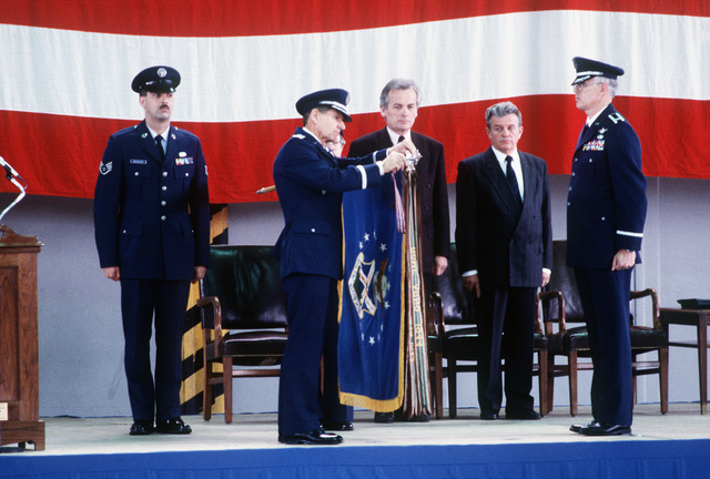 MGEN James E. Chambers, commander, 17th Air Force, attaches the Outstanding Unit Award to the colors of the 26th Tactical Reconnaissance Wing (26th TRW) during the wing's inactivation ceremony. Looking on are Rudi Geil, center, minister of the interior for the state of Rheinland Pfalz; Werner Vonblon, second from right, mayor of the city of Zweibrucken; and COL Kenneth Funkhauser, right, commanding officer of the 26th TRW