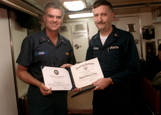 Assistant CHIEF of Naval Operations (Undersea Warfare) VADM Roger F. Bacon, left, and MCPO Brigham hold up Brigham's discharge and re-enlistment certificates following a ceremony aboard the nuclear-powered attack submarine USS PARGO (SSN-650). The PARGO is underway north of the Arctic Circle.