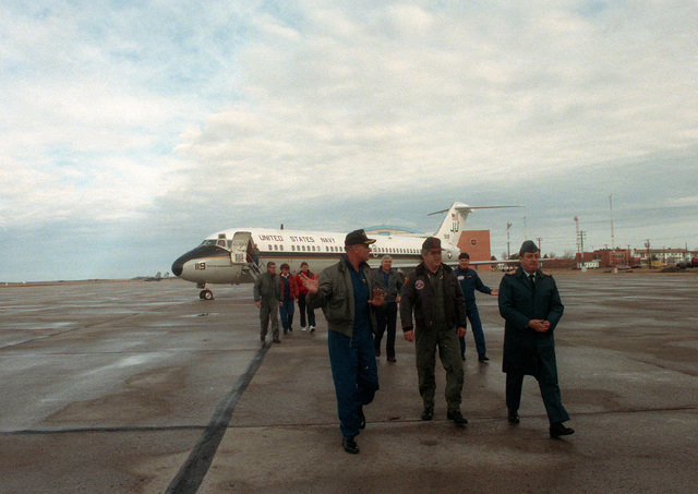 Assistant CHIEF of Naval Operations (Undersea Warfare) VADM Roger F. Bacon, left, and Undersecretary of the Navy Daniel Howard, center, are escorted by a Canadian officer after disembarking from a Fleet Logistic Support Squadron 56 (VR-56) C-9B Skytrain II aircraft during a stopover at the base. Bacon and Howard are part of an official party en route to visit the nuclear-powered attack submarine USS PARGO (SSN-650) north of the Arctic Circle.