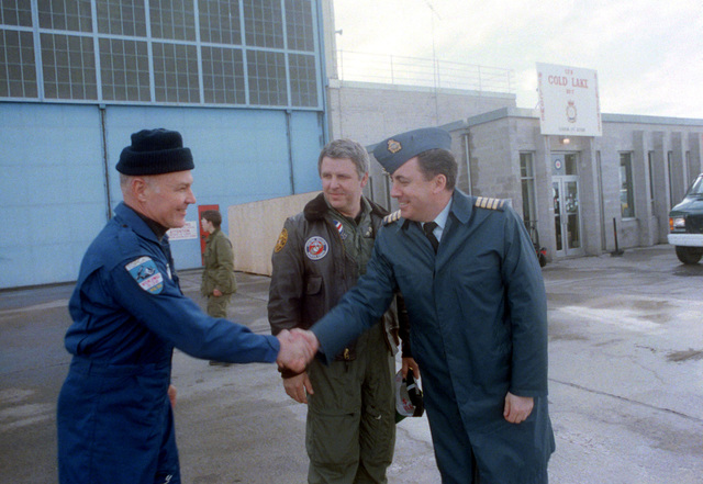 Undersecretary of the Navy Daniel Howard, center, watches as VADM Henry G. Chiles Jr., left, commander, Submarine Force, U.S. Atlantic Fleet, is greeted by a Canadian officer during a stopover at the base. Howard is leading an official party en route to visit the nuclear-powered attack submarine USS PARGO (SSN-650) north of the Arctic Circle.