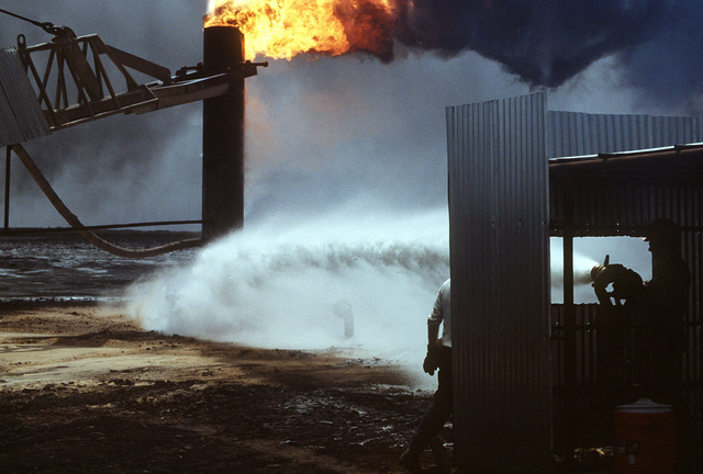 Firefighters from the Boots and Coots Oil Well Firefighting Company pour water on a blazing well after capping it in the aftermath of Operation Desert Storm. The well, situated in the Ahman Oil Fields, is one of many set afire by Iraqi forces prior to their retreat from Kuwait.