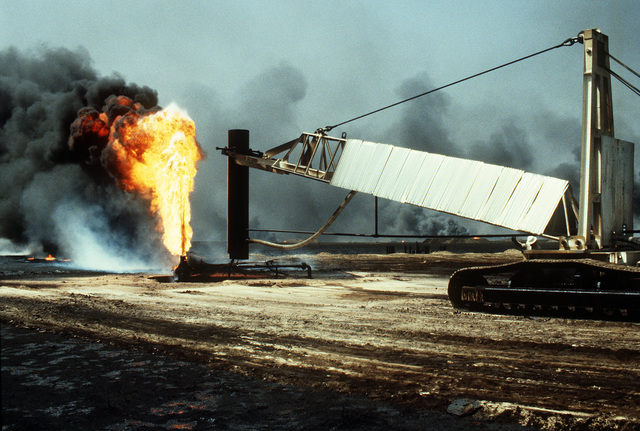 Firefighters from the Boots and Coots Oil Well Firefighting Company prepare to position a cap on a blazing well in the aftermath of Operation Desert Storm. The well, situated in the Ahman Oil Fields, is one of many set afire by Iraqi forces prior to their retreat from Kuwait.