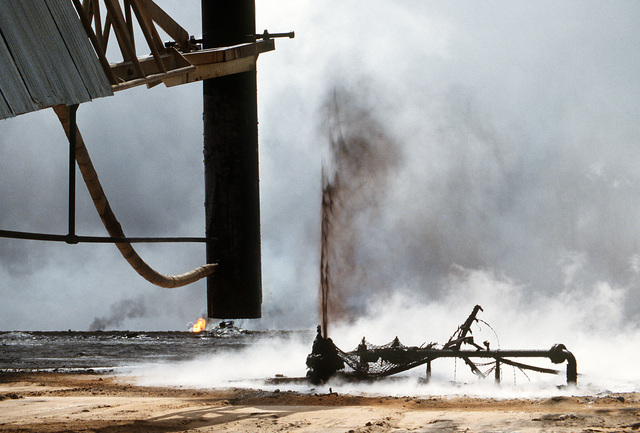 Firefighters from the Boots and Coots Oil Well Firefighting Company use a crane to remove a capping device after extinguishing a burning oil well in the aftermath of Operation Desert Storm. The well, situated in the Ahman Oil Fields, is one of many set afire by Iraqi forces prior to their retreat from Kuwait.