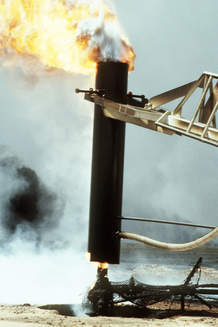 Firefighters from the Boots and Coots Oil Well Firefighting Company use a crane to cap a blazing well in the aftermath of Operation Desert Storm. The well, situated in the Ahman Oil Fields, is one of many set afire by Iraqi forces prior to their retreat from Kuwait.