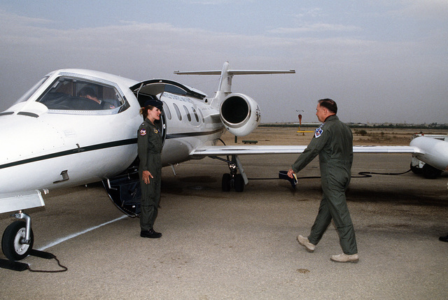 First LT. Jennifer Bier, 1402nd Military Airlift Squadron, stands at attention as LT. GEN. Charles Horner, commanding general, U.S. Central Air Force, prepares to board a C-21A Learjet aircraft. Horner is visiting various coalition countries in the aftermath of Operation Desert Storm.