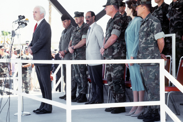 Sen. John McCain of Arizona speaks during a ceremony welcoming Kuwaiti Ambassador Sheik Saud Nasir Al-Sabah to the base. Standing behind the senator are, from left: COL D.P. DeLong, commander, Marine Aviation Weapons and Tactics Squadron 1 (MAWTS-1); COL C.B. Cheatham, commander, MCAS, Yuma; BGEN W.T. Adams, commander, Marine Corps Air Bases, West; Suzie White, wife of LTC White, commander, Marine Attack Squadron 311 (VMA-311); and COL J. Anderson, commander, Marine Air Group 13 (MAG-13)