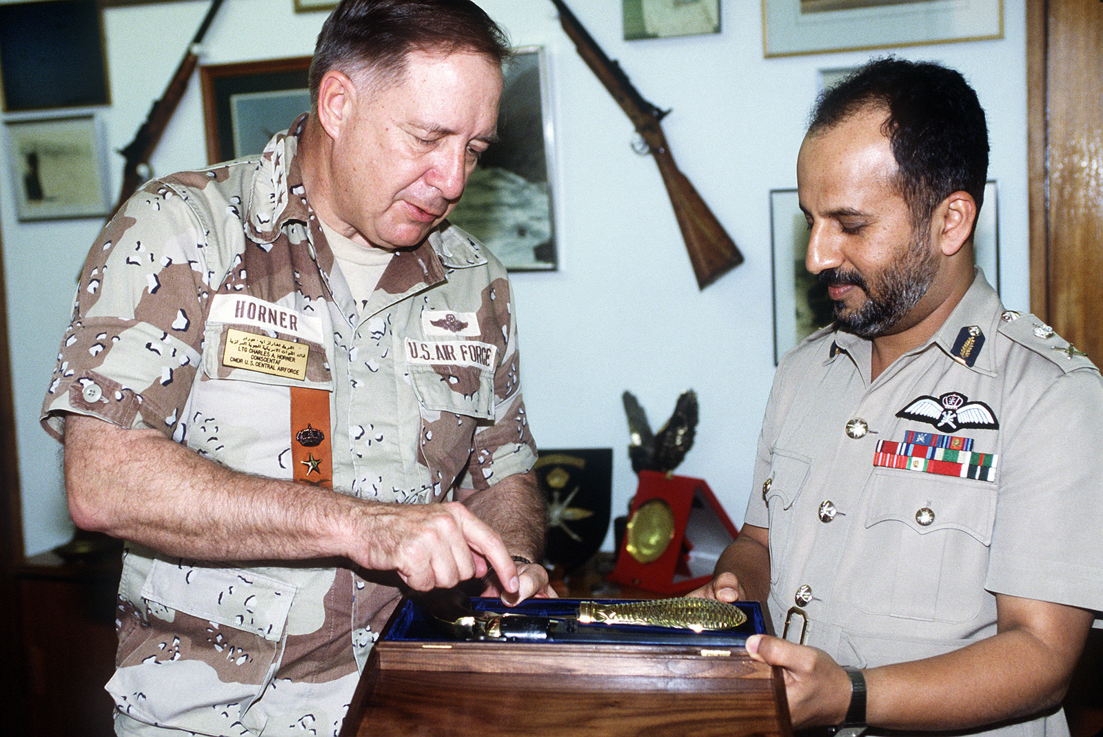 LT. GEN. Charles A. Horner, commanding general, U.S. Central Air Force, presents Air Vice Marshal Talib Bin Miran Bin Zamam Al-Raeesi with a pistol in recognition of his performance during Operation Desert Storm.