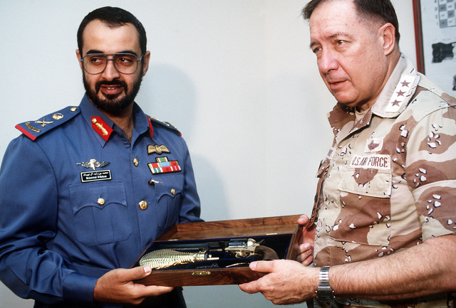 LT. GEN. Charles A. Horner, commanding general, U.S. Central Air Force, presents Mohammad Al-Nahyan, a United Arab Emirates air force officer, with a pistol in recognition of his performance during Operation Desert Storm.