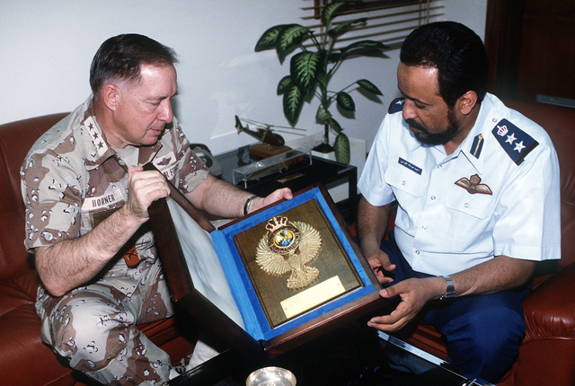 LT. GEN. Charles Horner, commanding general, U.S. Central Air Force, receives a plaque from COL. Ahmed Al-Kuwari, Qatari base commander, during his visit to the base in the aftermath of Operation Desert Storm.