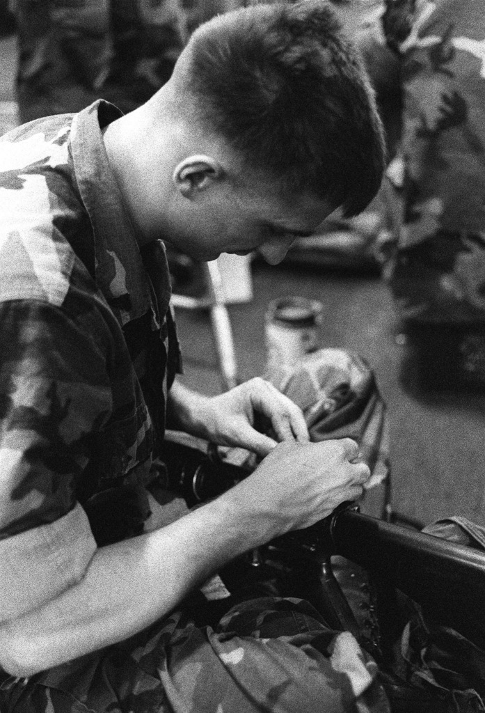 A Marine cleans his XM-249E1 squad automatic weapon (SAW) aboard a U.S. Navy ship as he prepares for relocation to an outlying camp during Operation Provide Comfort, an Allied effort to aid Kurdish refugees who fled from the forces of Saddam Hussein in northern Iraq