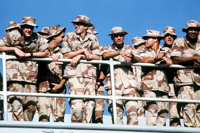 Marines from the 4th Marine Expeditionary Brigade (4th MEU) crowd along a railing aboard an amphibious ship as it arrives at the pier. The Marines, who were deployed aboard the ship for Operation Desert Shield and Operation Desert Storm, will disembark at Morehead City to return to Marine Corps Base, Camp Lejeune, N.C