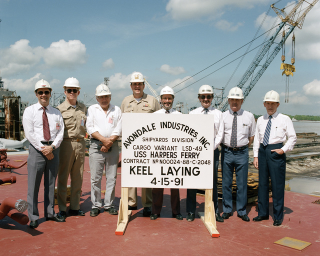 Representatives of Avondale Industries, Inc., and US Navy officials pose for a photograph at the keel laying ceremony for the dock landing ship USS HARPERS FERRY (LSD 49). They include, from left: C. Sprague, LSD 44/48 Prog. Mgr.'s Rep.: Emile Foret, Vice President, Ship Construction; Captain John C. Donohue, SSNO, Supervisor of Shipbuilding; Carey Agregaard, Asst. Prog. Mgr.; David Gordon, LSD (CV) Prog. Mgr.; R. Clark, Lead Production Engineer and P.O. Potter, Configuration Mgr.