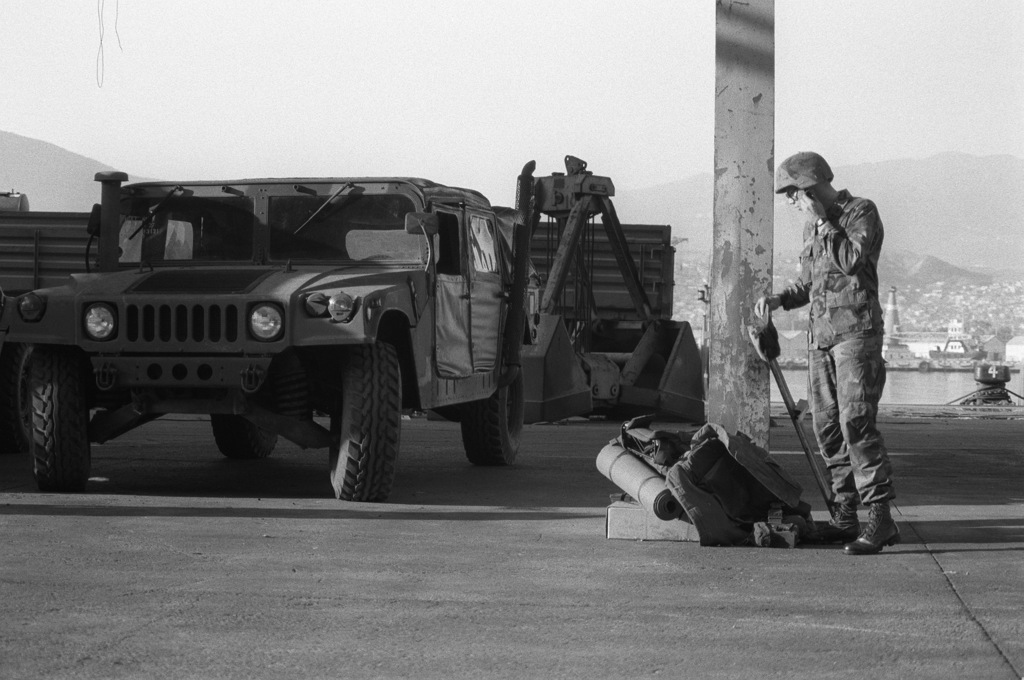 A Marine stands by an M998 High-Mobility Multipurpose Wheeled Vehicle (HMMWV) following its offloading from a US Navy ship. Equipment is being offloaded for use during Operation Provide Comfort, an Allied effort to aid Kurdish refugees who fled from the forces of Saddam Hussein in northern Iraq
