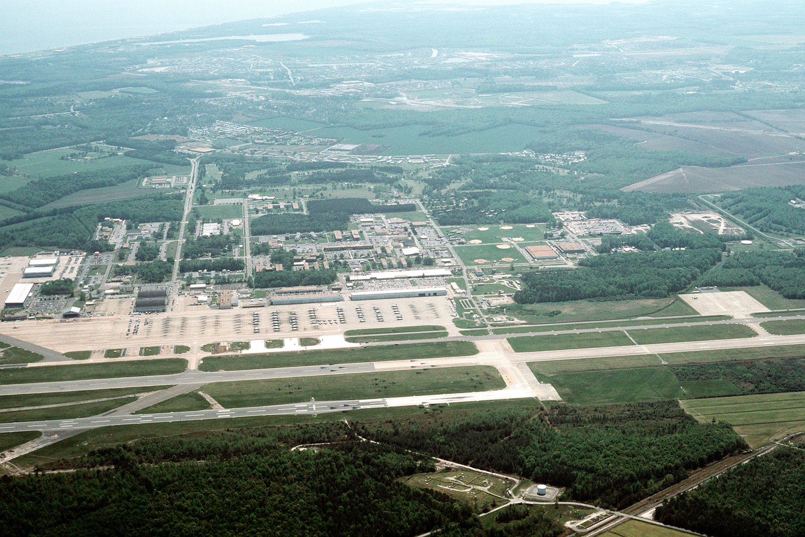 An aerial view of a portion of the air station. On and between the runways are the shadows of F-14A Tomcat aircraft and A-6E Intruder aircraft from Carrier Air Wing (CVW-1). The aircraft are returning to Oceana after their deployment to the Persian Gulf region aboard the aircraft carrier USS AMERICA (CV-66) for Operation Desert Shield and Operation Desert Storm